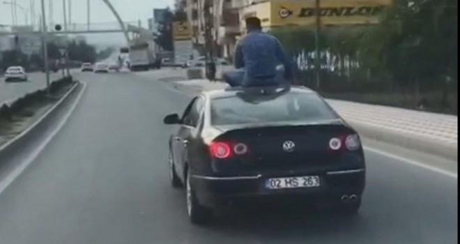 Otomobilin üstüne oturarak yolculuk yaptı